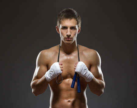 Half-length portrait of sexy sportsman keeping a string with his hands wrapped with elastic bandage, isolated on black photo