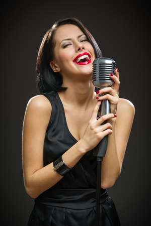 Half-length portrait of female musician with closed eyes wearing black evening dress and keeping mic on grey background. Concept of music and retro fashion photo