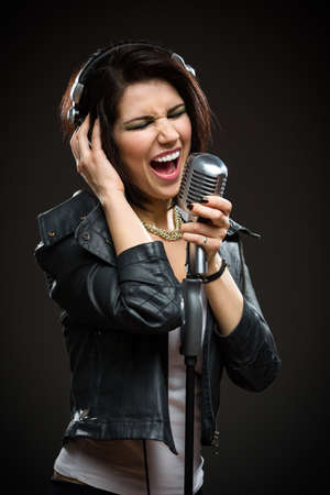 Half-length portrait of female rock singer with microphone and earphones. Concept of rock music and rave photo