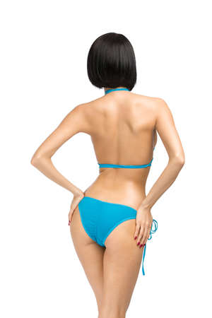 Backview of female wearing bikini, isolated on white. Concept of summer holidays and traveling photo