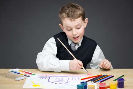 Portrait of little boy drawing something with paints and pencils. Concept of arts and hobby photo