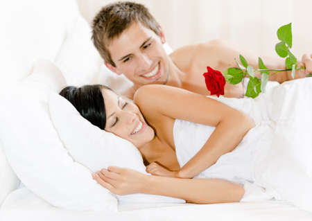 gives: Man lying in bed gives red rose to woman. Concept of love and affection