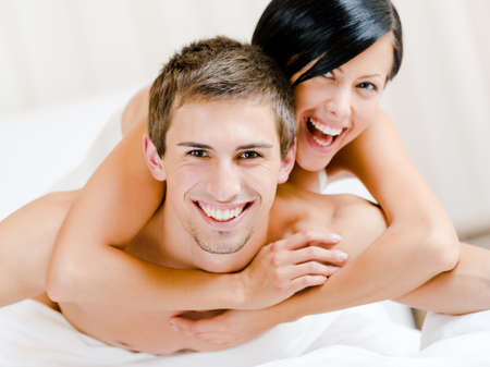 close in: Close up of laughing couple who plays in bed. Woman lying on the back of the man embraces him Stock Photo