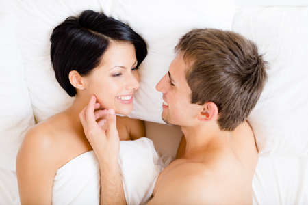 Close up of man stroking woman lying in bed, top view. Concept of love and affection photo