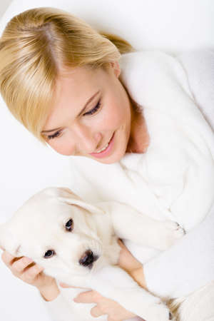 Top view of woman in white sweater with Labrador puppy sitting on her hands photo