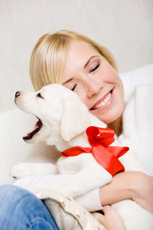 Woman embracing white puppy with red ribbon on the neck photo