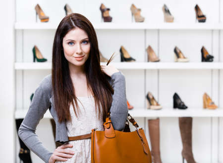 Portrait of woman in shopping center in the section of female footwear. Concept of consumerism and stylish purchase photo