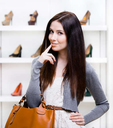 Portrait of woman in shopping center in the section of female high heeled shoes. Concept of consumerism and stylish purchase photo