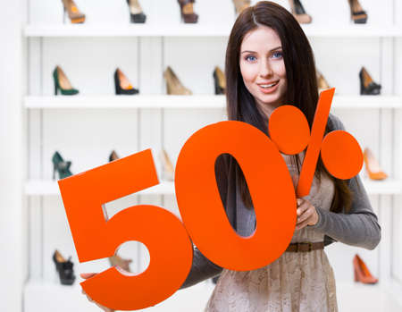 Woman keeps the model of 50% sale on shoes standing at the shopping center against the showcase with pumps photo