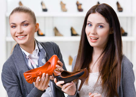 Salesperson offers heeled shoes for the female customer in the shopping center photo