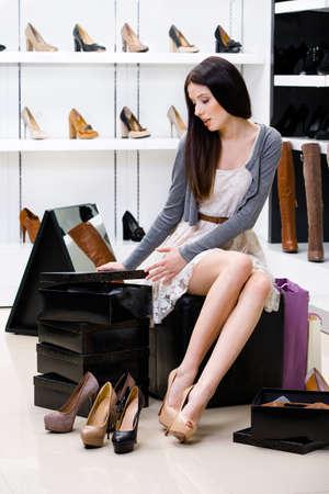 Frau sitzt auf dem Stuhl und versucht auf Pumpen im Shop kann sich nicht entscheiden, was zu kaufen Lizenzfreie Bilder