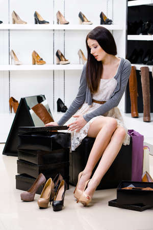 Woman sitting on the chair and trying on pumps in the shop cant decide what to buy photo