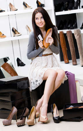 Woman hands shoes and credit card in the footwear shop where she would like to buy new pumps