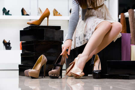high view: Female legs and variety of shoes in the footwear shop