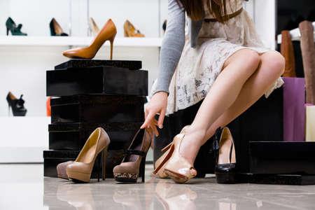comprando zapatos: Piernas femeninas y variedad de zapatos en la tienda de calzado Foto de archivo