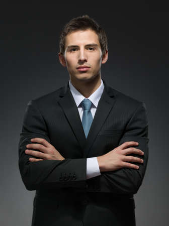professionalism: Half-length portrait of businessman with his crossed arms. Concept of professionalism and business success
