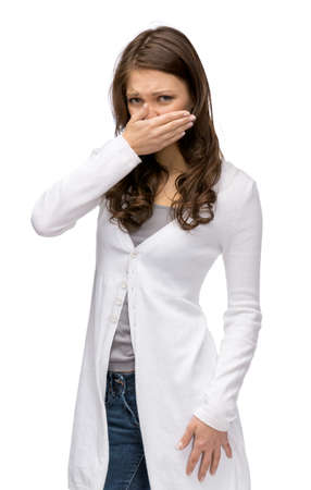 Portrait of girl covering her nose, isolated on white. Concept of stink and disgust photo