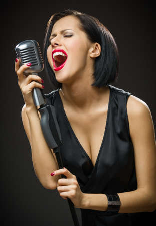 Half-length portrait of female musician with closed eyes wearing black evening dress and keeping microphone on grey background. Concept of music and retro fashion photo