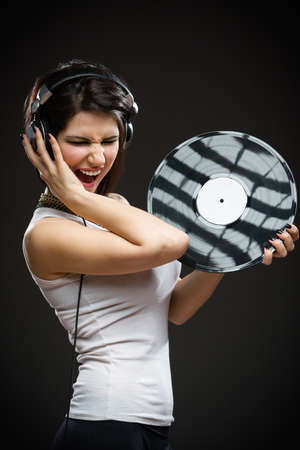 Half-length portrait of pretty teenager with earphones and record in hands on grey background. Concept of rock music and arts photo