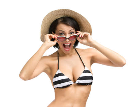 Half-length portrait of woman wearing bikini, hat and sunglasses, isolated on white. Concept of summer holidays and traveling photo