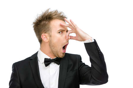 detestable: Portrait of businessman covering his nose, isolated on white. Concept of stink and disgust Stock Photo