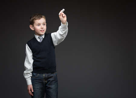 Portrait of boy writing something with chalk on grey background, copyspace Stock Photo - 25536467