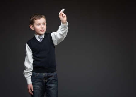 Portrait of boy writing something with chalk on grey background, copyspace Stock Photo - 25536467