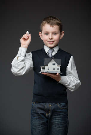 architecting: Portrait of boy writing something with chalk and keeping home model on grey background