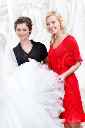 Two girls touch the wedding dress hesitating about fitting. White background photo
