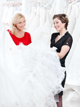 bridal salon: Two girls are talking about the wedding dress preparing to try it on.