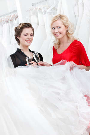 Two girls drink spirits while discussing and choosing the wedding gown photo
