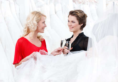 Two girls drink alcoholic drinks while discussing and choosing the wedding gown photo
