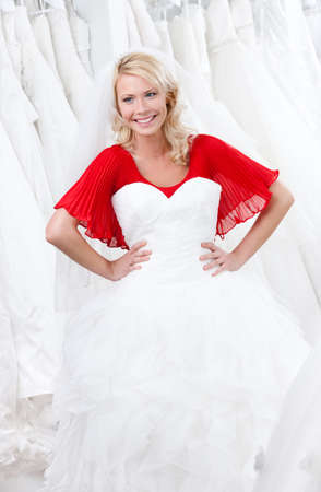 decides: Young girl puts a wedding gown to her body, deciding whether it suits for her or not