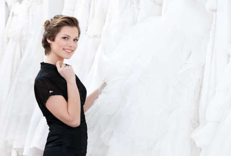 making dresses: Shop assistant thinks about dress recommendation to the bride, white background Stock Photo