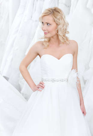 Youg girl is trying on a beautiful wedding gown, white background photo