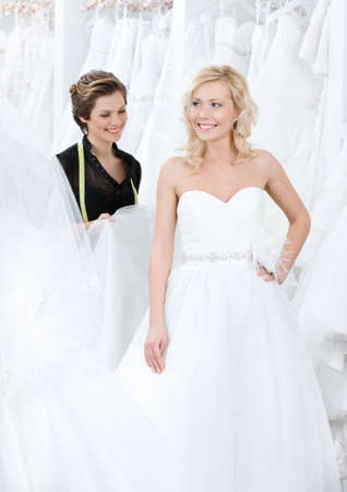 Future bride admires the wedding dress that suits her photo
