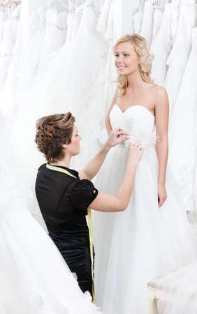 lanzamiento de bala: Costurera mide la cintura de la novia para encajar el vestido Foto de archivo