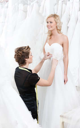 Seamstress measures waist of the bride to fit the dress
