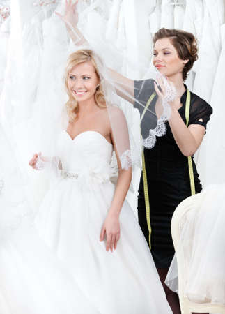 Shop assistant puts wedding veil on the head of the bride, white background photo