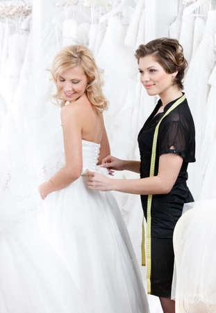 lanzamiento de bala: Ayudante de departamento ayuda a la novia a ponerse el vestido de novia en Foto de archivo