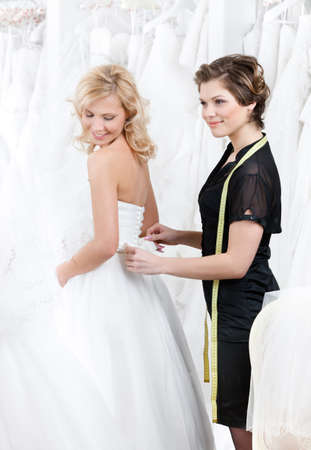 Shop assistant helps to the bride to put the wedding dress on photo