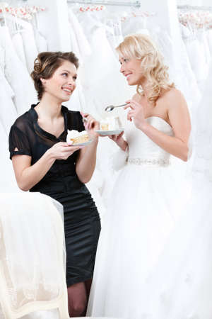 Shop assistant and the bride eat a pie selebrating a good decision photo