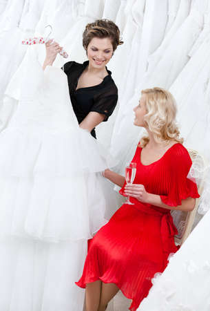 Shop assistant offers another dress to the bride while she is drinking champagne photo