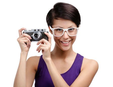 Creative girl in spectacles hands retro photographic camera, isolated on white photo