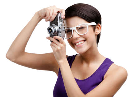 Creative woman in spectacles hands retro photographic camera, isolated on white photo