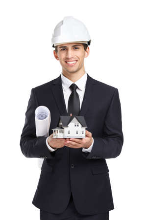 Businessman in white helmet hands model house and layout, isolated on white. Concept of real estate and engineering photo