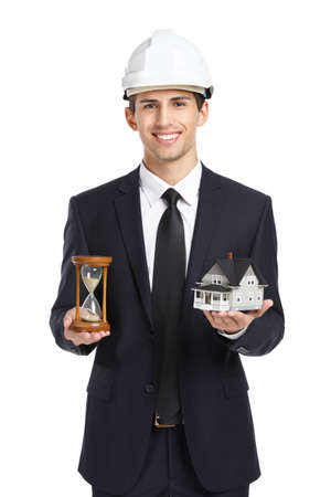 architecting: Real estate agent wearing white helmet hands model house and hourglass, isolated on white Stock Photo