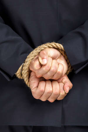Close up of tied hands of businessman. Concept of slavery and hard work photo