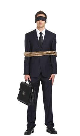 Full-length portrait of blind-folded businessman tied with the line, isolated on white. Concept of slavery and violence photo