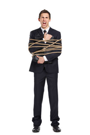 servitude: Full-length portrait of businessman screaming and handing briefcase who tied with the rope, isolated on white. Concept of slavery and violence Stock Photo